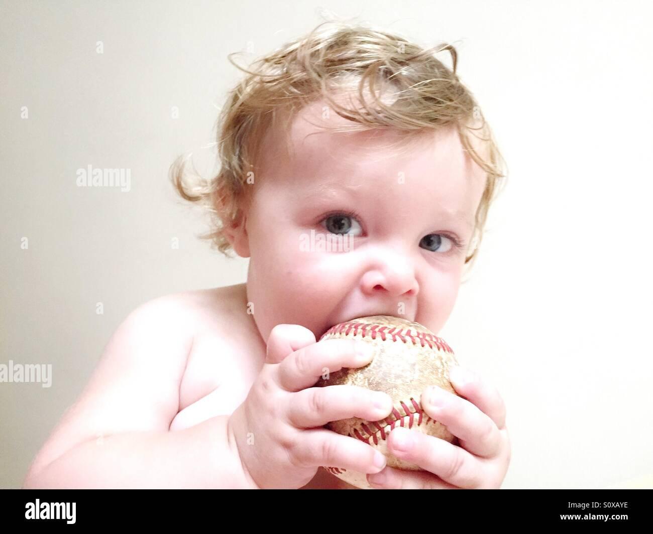 Hohen Schlüsselbild einen Babyjungen kauen auf einer alten baseball Stockbild