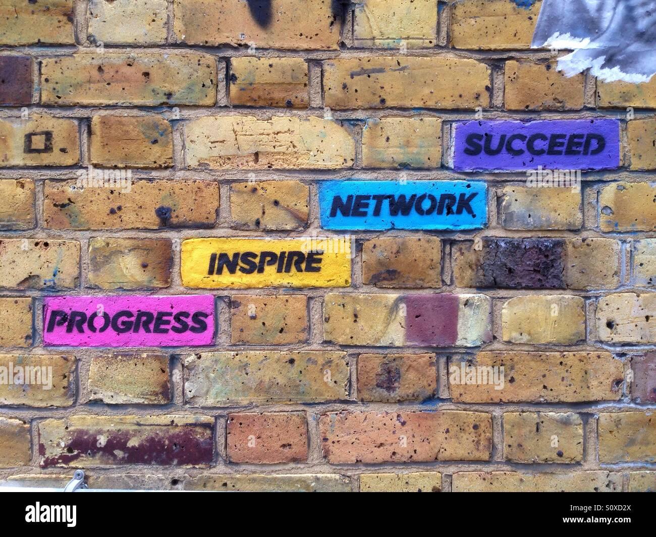 Street-Art im Bereich der Brick Lane, Shoreditch, East London, UK: farbige Ziegel mit inspirierende Konzepte Fortschritt Stockbild