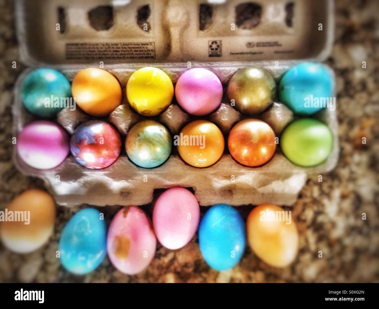 Und ein halbes Dutzend farbigen Eiern in einem Pappkarton. Stockbild