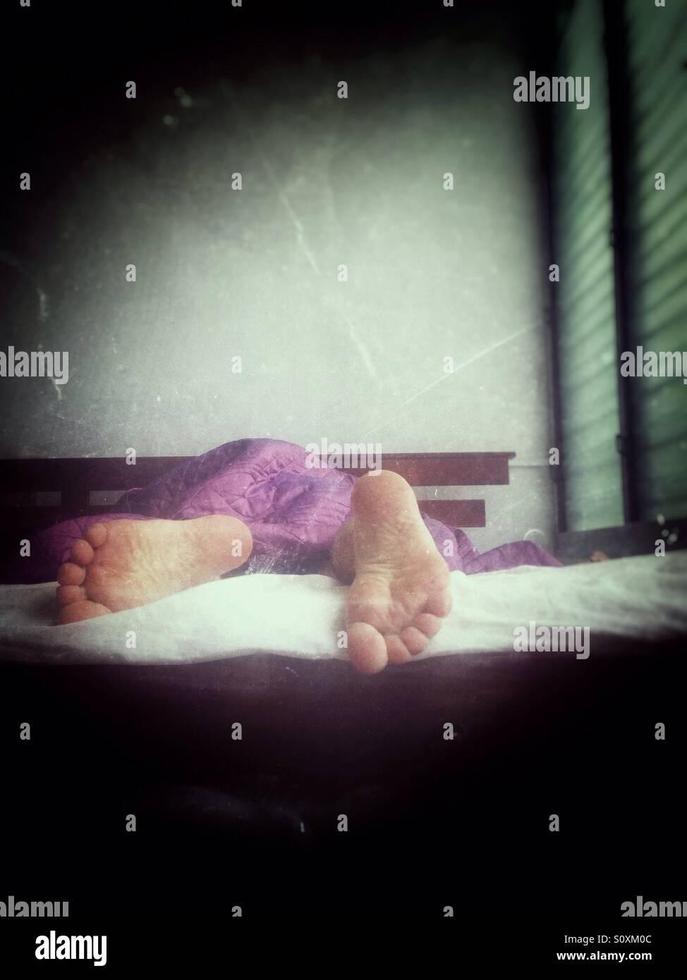 Füße eines schlafenden Mannes. Stockbild