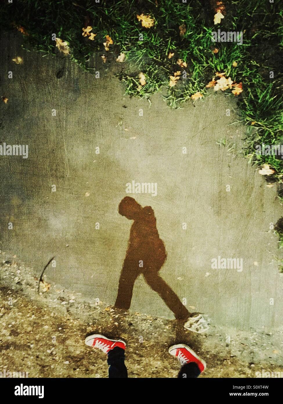 Junge Silhouette zu Fuß mit roten converse Stockbild