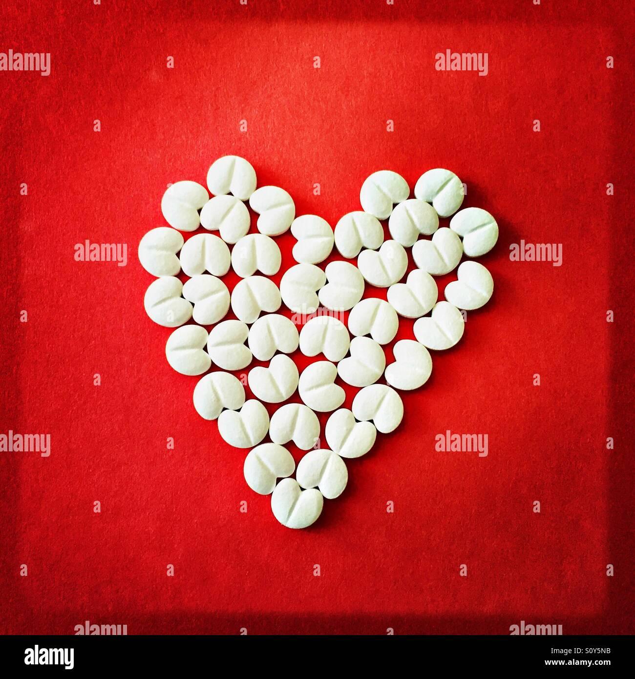 Herzförmigen Tabletten auf rotem Grund Stockfoto