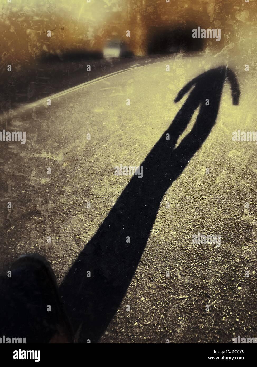 Der lange Schatten eines Mannes zu Fuß eine Straße hinunter. Stockbild