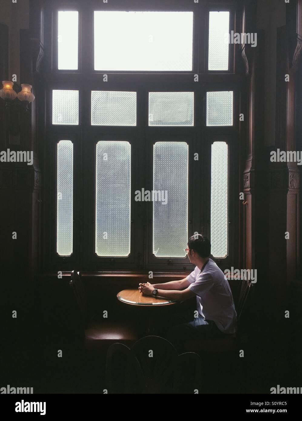 Mann schaut aus einem Fenster in einem café Stockbild
