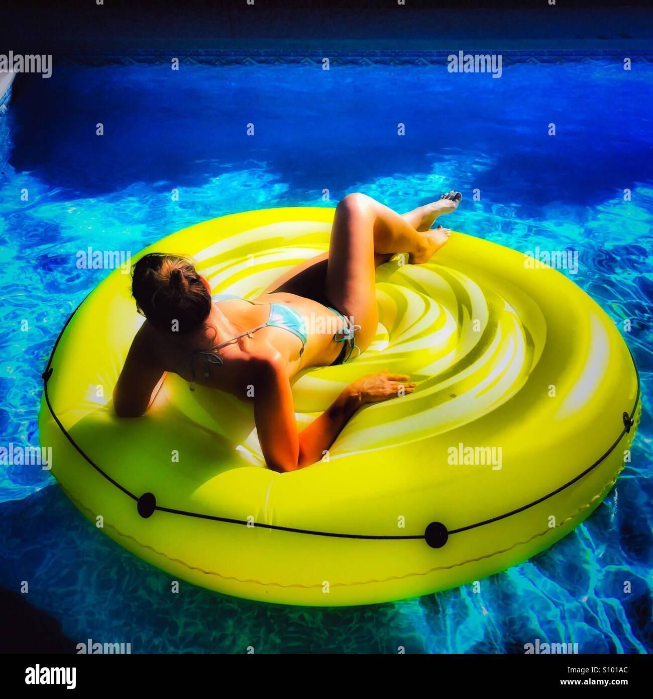 Frau auf einem aufblasbaren Poolspielzeug an einem heißen sonnigen Tag entspannen. Quadratische Ernte. Natürliches Stockbild