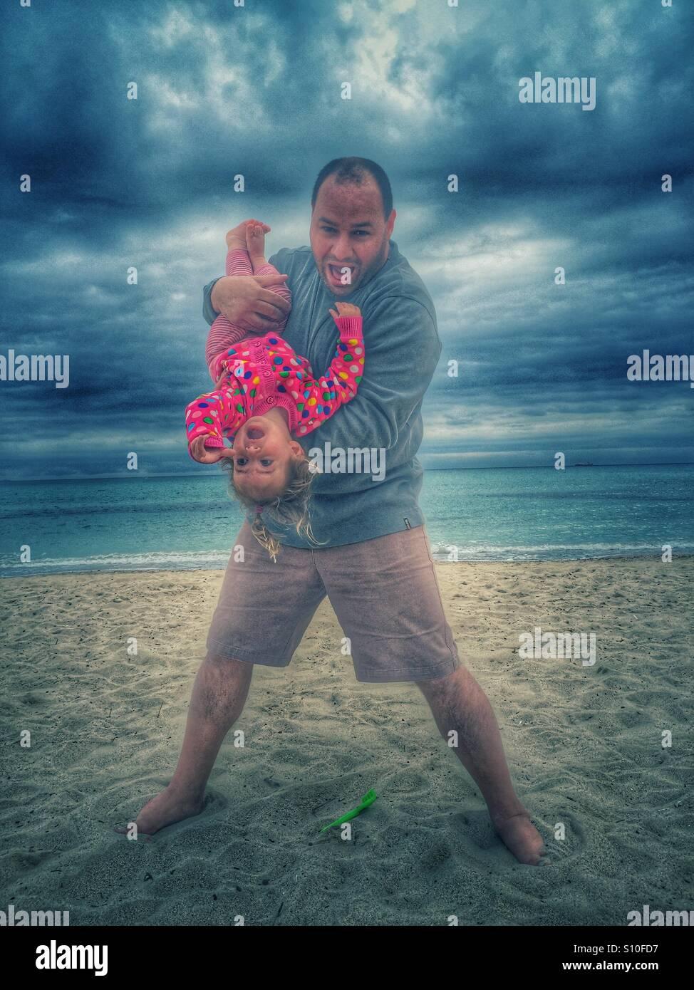 Vater und Baby Mädchen spielen am Strand Stockbild
