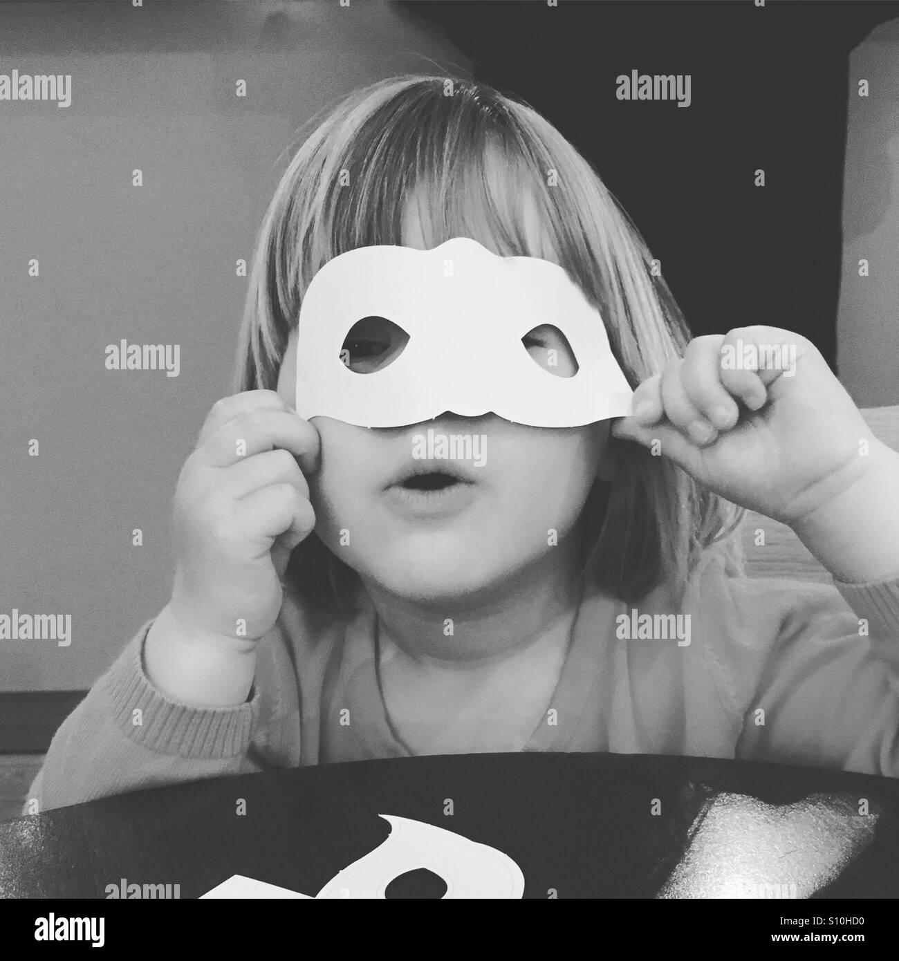 Kleinkind mit Maske Stockbild