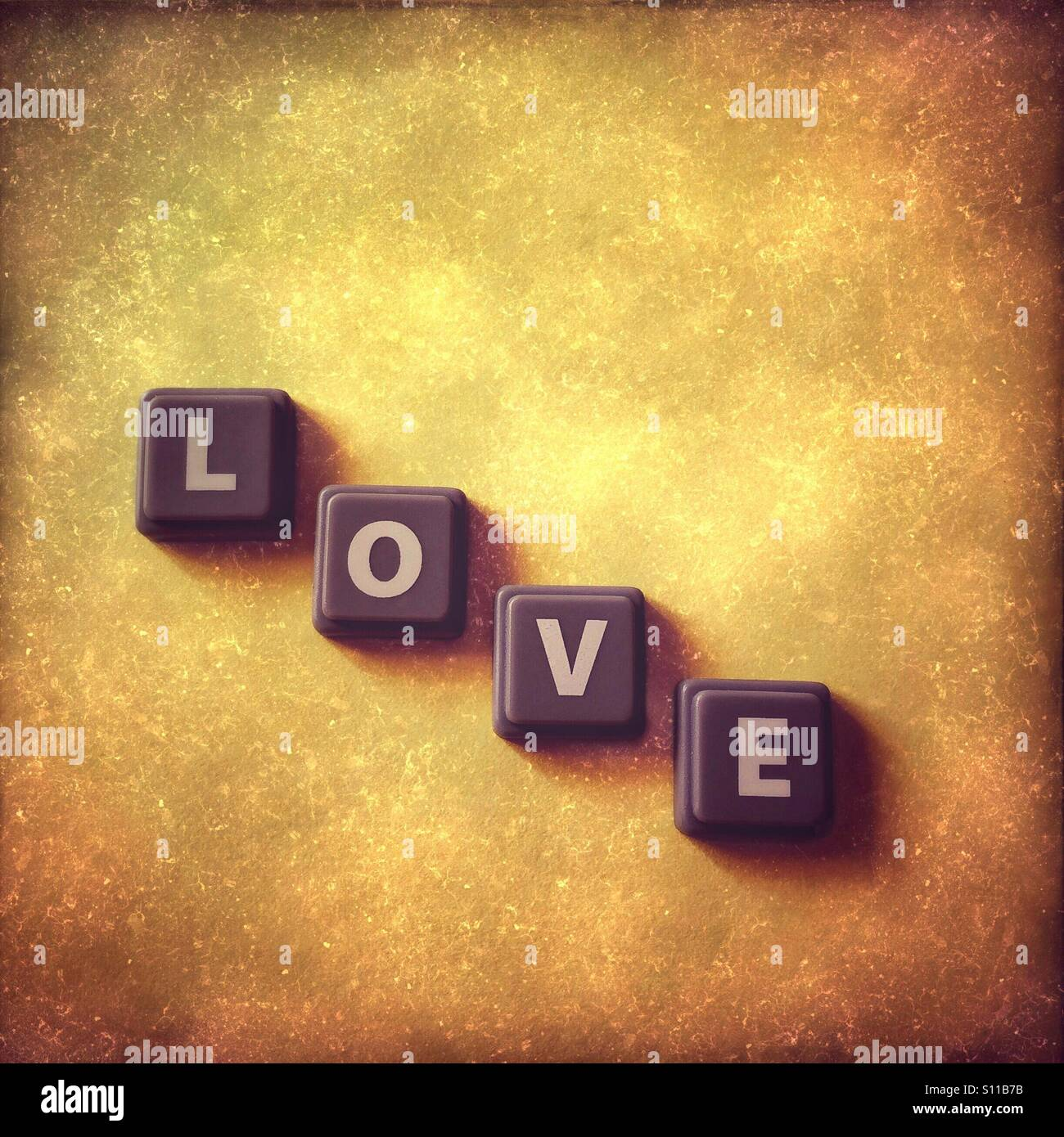 Wort-Liebe auf gelben Grunge Hintergrund Stockfoto