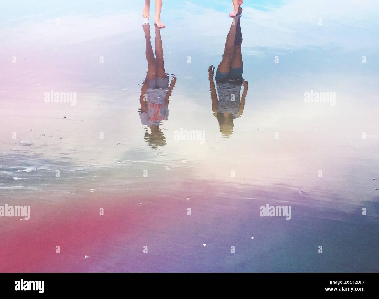 Die Reflexionen der beiden dunkelhaarigen Schwestern im Sand am Strand Stockbild