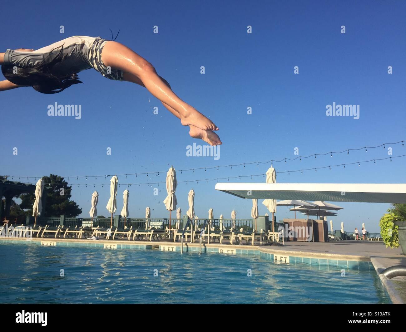 Ein Kind taucht anmutig und rückwärts ein Sprungbrett in einen blauen Pool. Stockbild