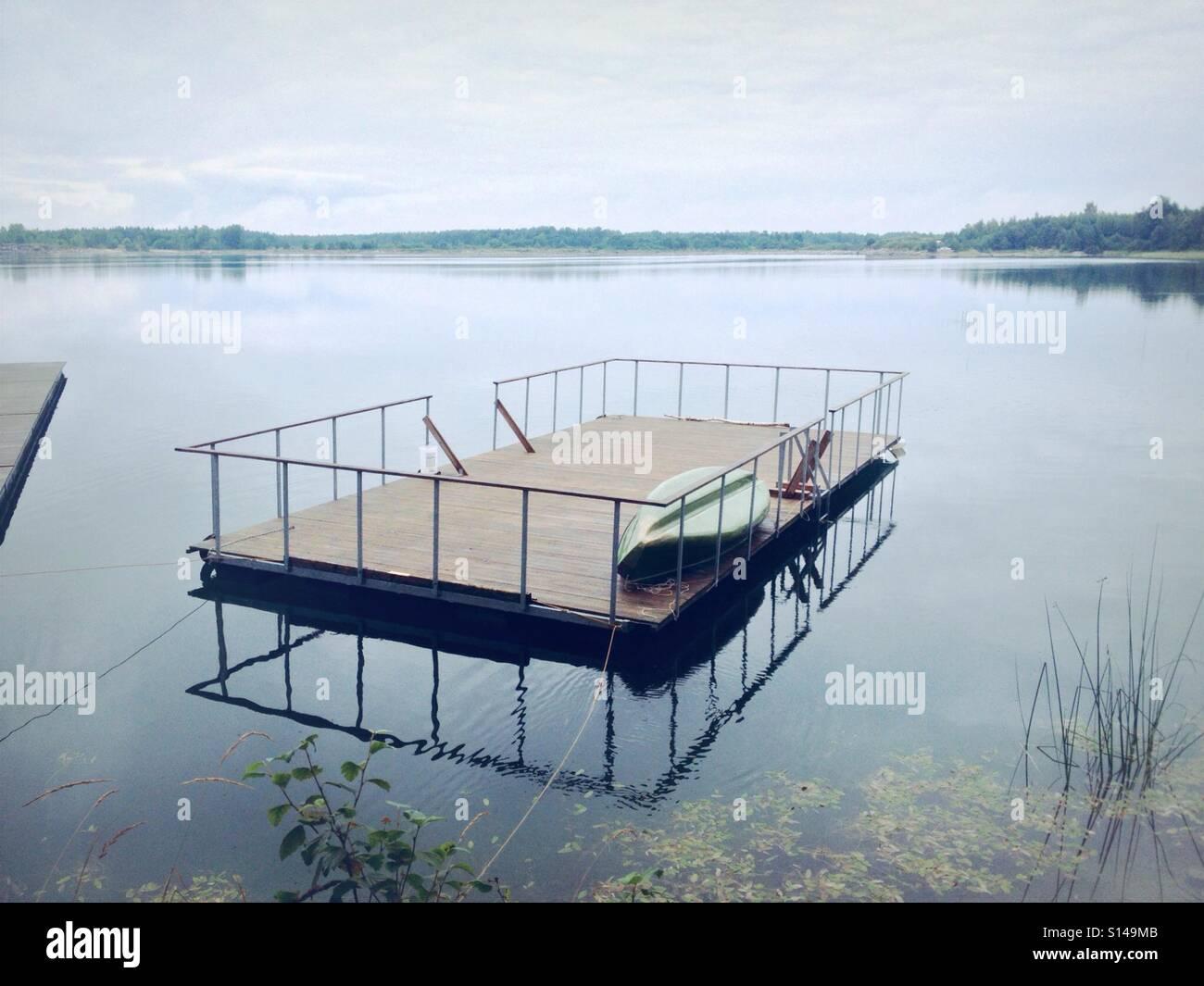 Schwimmenden Floß auf klarem Wassersee mit Spiegelreflexionen Stockbild