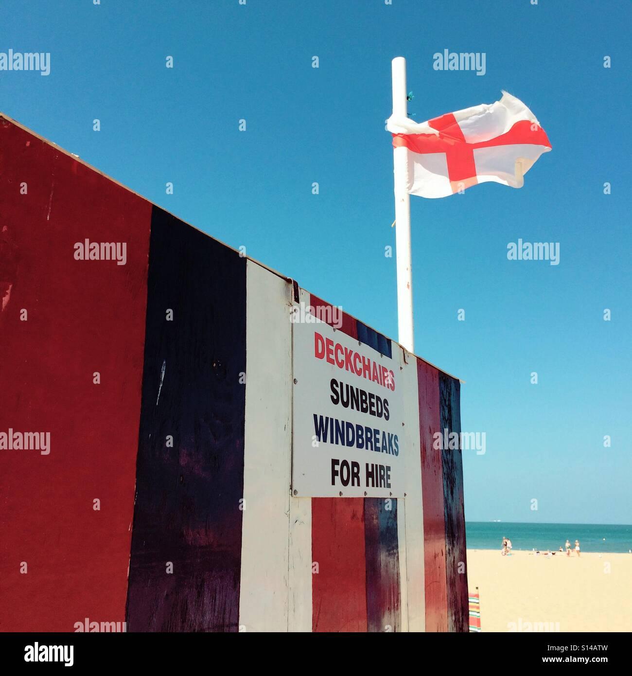 Liegestühlen Sonnen Betten Windschutzscheiben zu mieten auf einem englischen Strand Stockbild