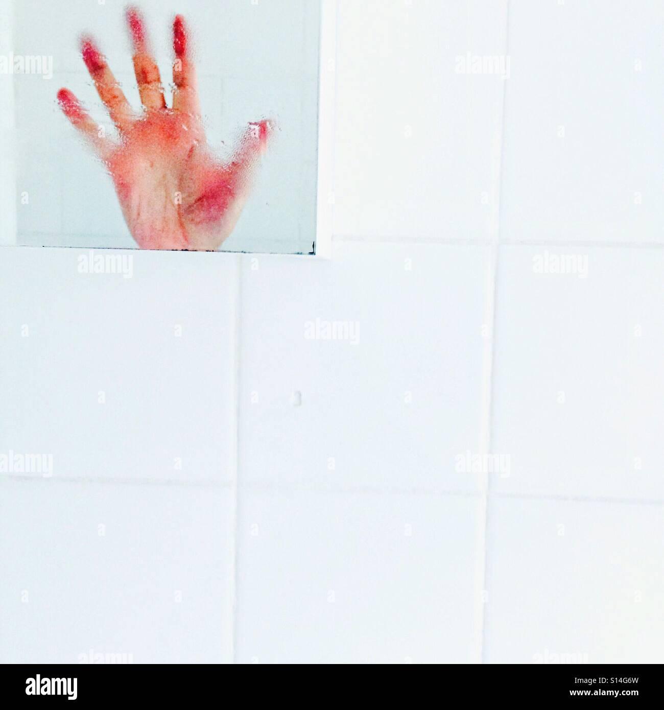 Hände hoch!  Eine Hand auf weißen Fliesen in einem Badezimmerspiegel reflektiert Stockbild
