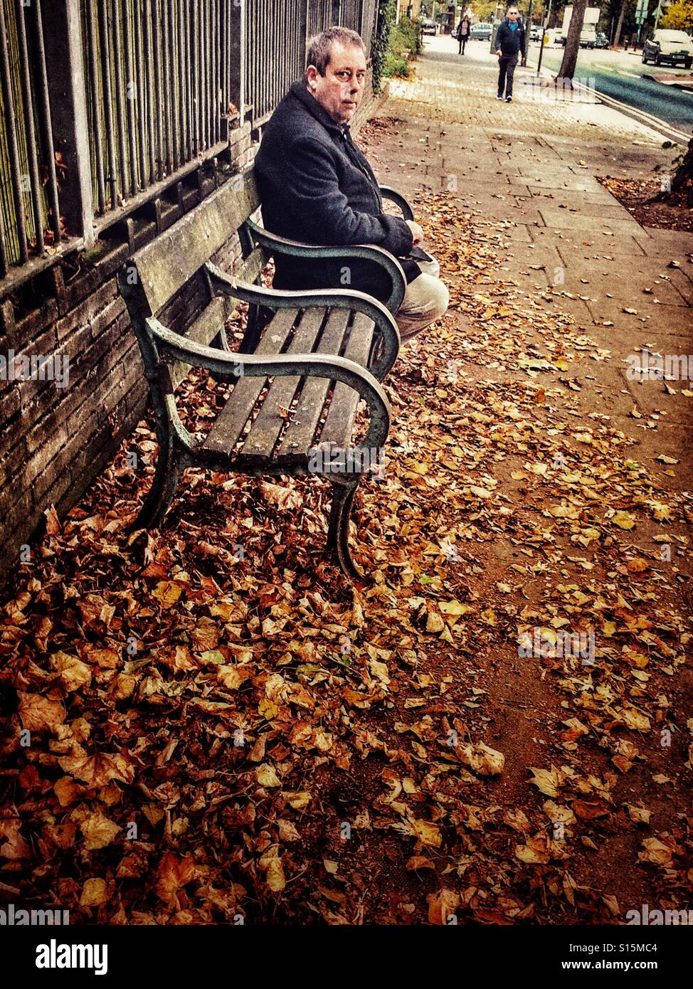 Mann auf einer Bank im Herbst Stockbild