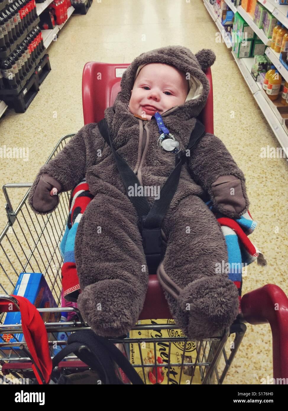 f8bda7cd366423 Drei Monate altes Baby junge trägt einen Anzug tragen. Sitzen in einem  Supermarkt Einkaufswagen