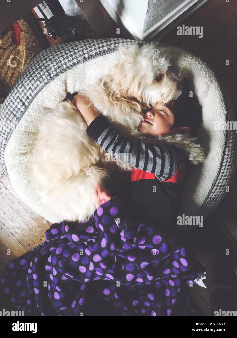 Junge und sein bester Freund kuscheln. Stockfoto