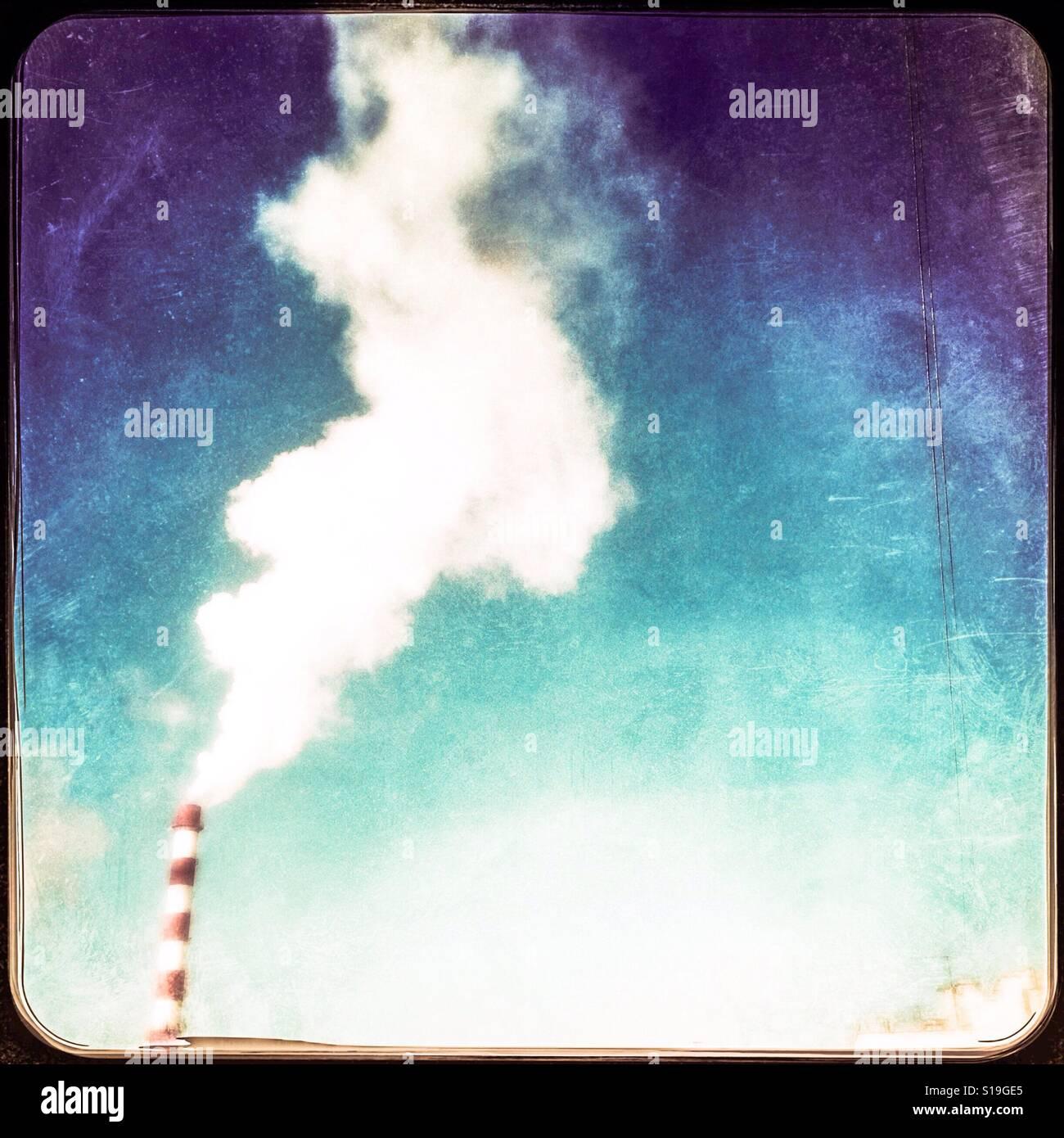 Rauch aus einem Schornstein, Kontrast bei blauem Himmel Stockbild