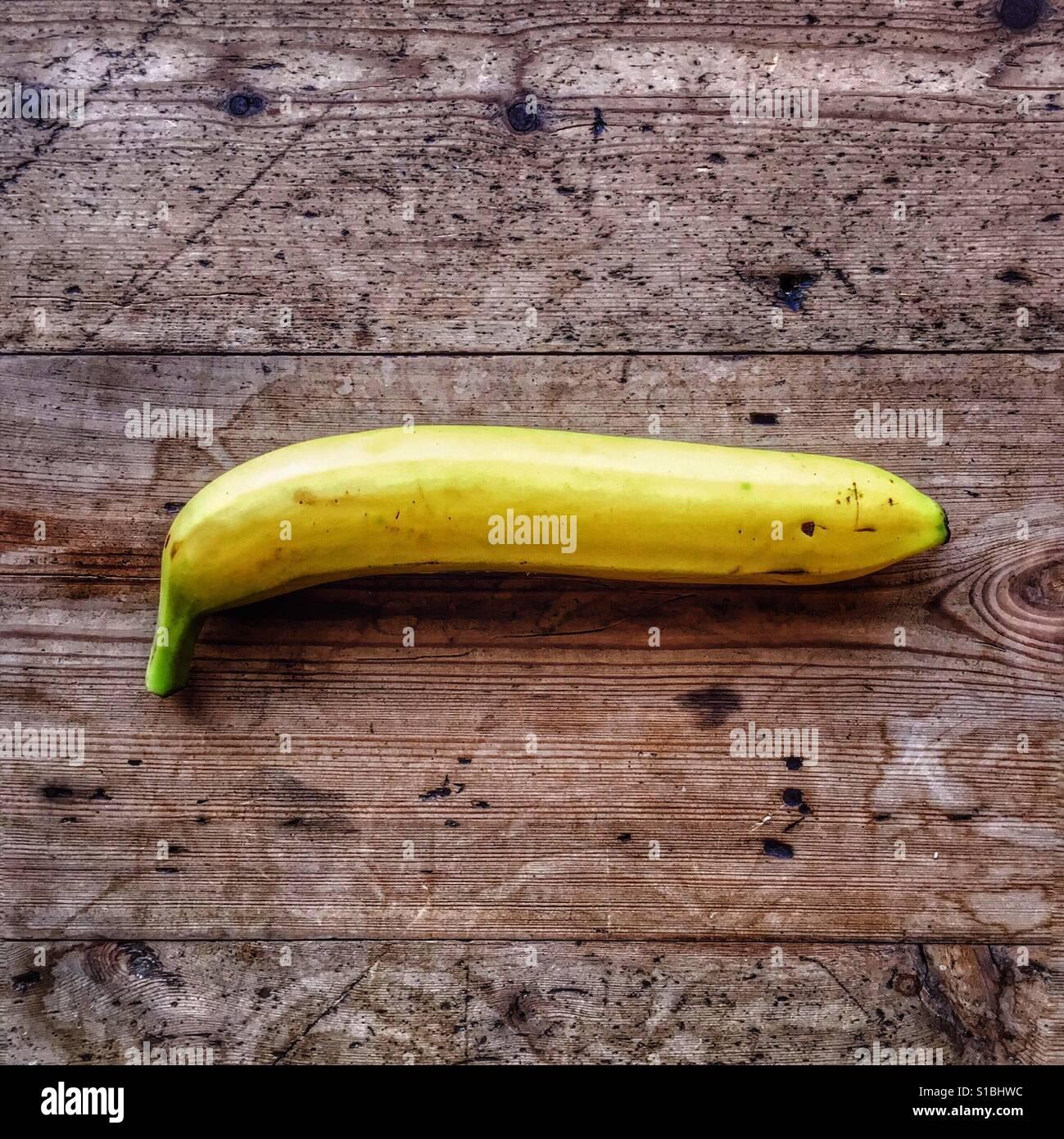 eine gerade banane ruht auf einer rustikalen holzoberfl che im nat rlichen tageslicht stockfoto. Black Bedroom Furniture Sets. Home Design Ideas