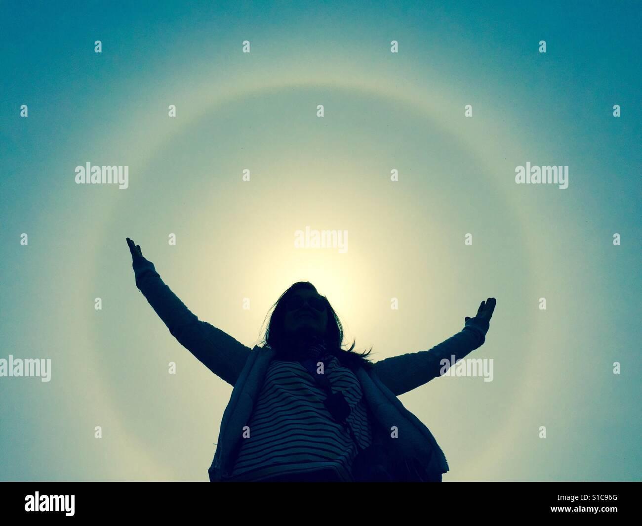 Innerhalb des Kreises eine Sundog steht eine Frau. Die Frau ist in der Silhouette. Stockbild