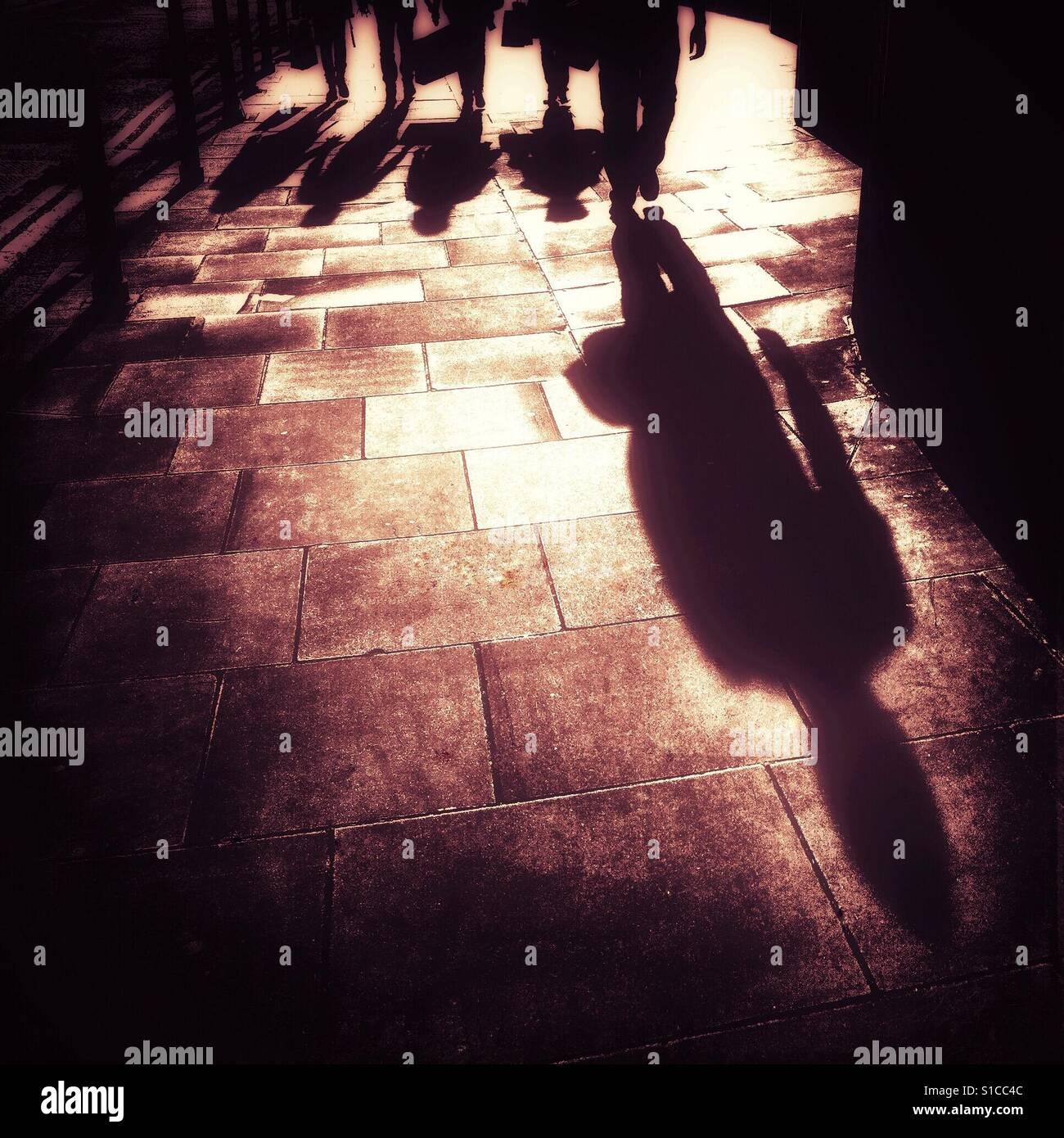 Der lange Schatten von einer Person zu Fuß entlang der Fahrbahn, dicht gefolgt von vier weiteren Personen in Stockbild
