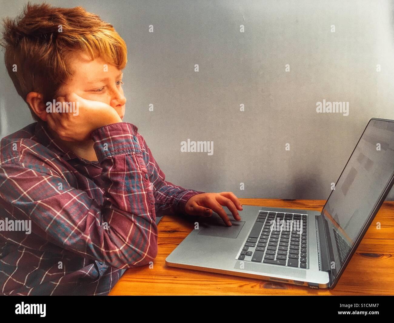 11-jährige Junge mit Laptop-computer Stockbild