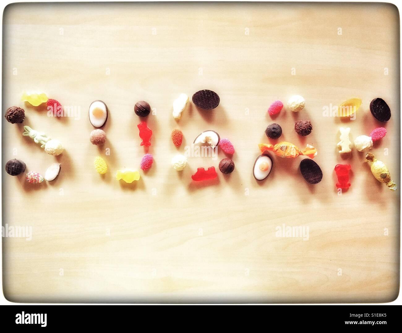 """Das Wort """"Zucker"""" mit Süßigkeiten und Bonbons auf einen hölzernen Hintergrund geschrieben Stockbild"""
