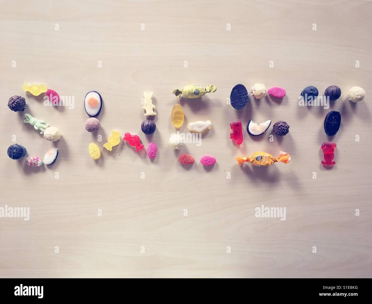 """Das Wort """"Sweet"""" mit Süßigkeiten und Bonbons auf einen hölzernen Hintergrund geschrieben Stockbild"""