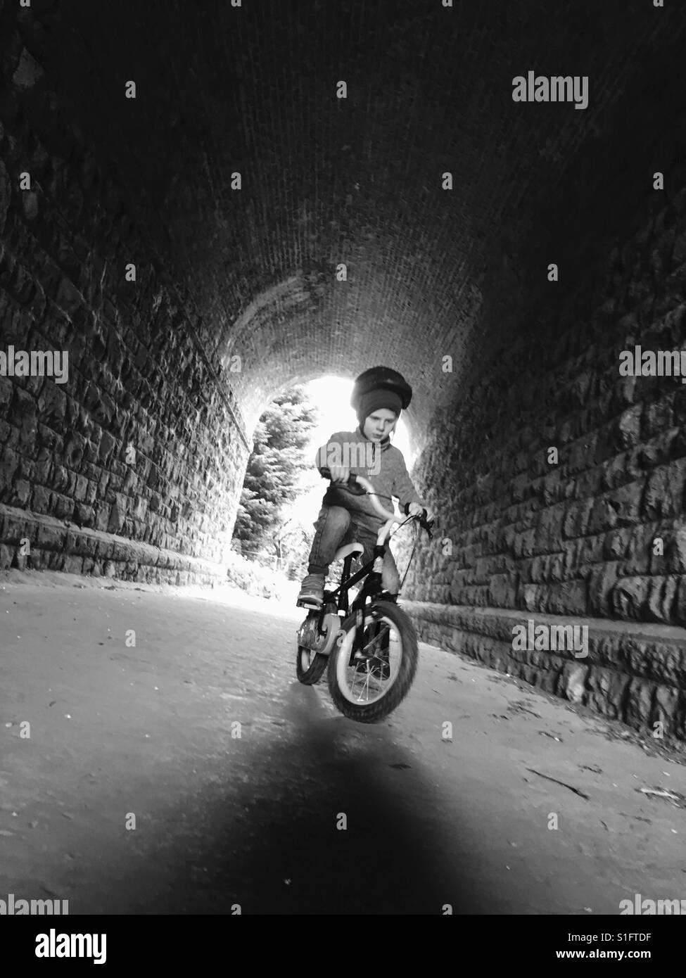 Junge mit dem Fahrrad durch tunnel Stockbild