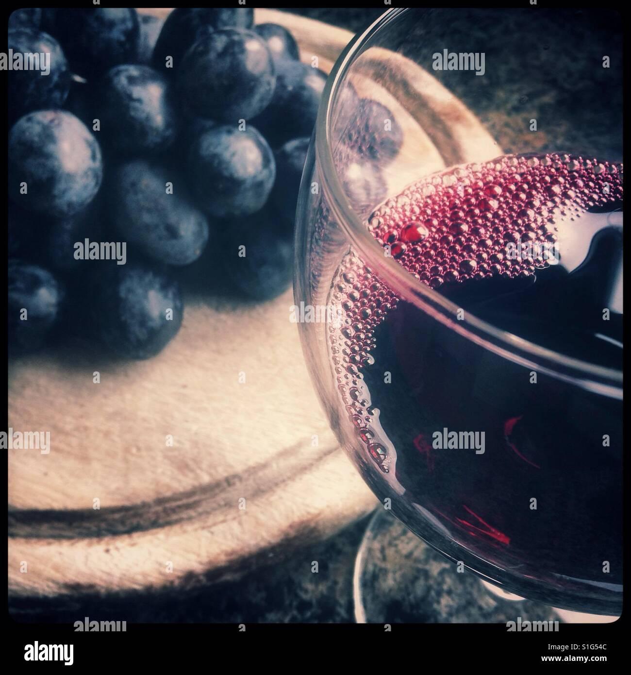 """Ein Glas Rotwein mit einigen """"Herbst Royal"""" [Essen] Tafeltrauben auf einem Holzbrett. Stockbild"""