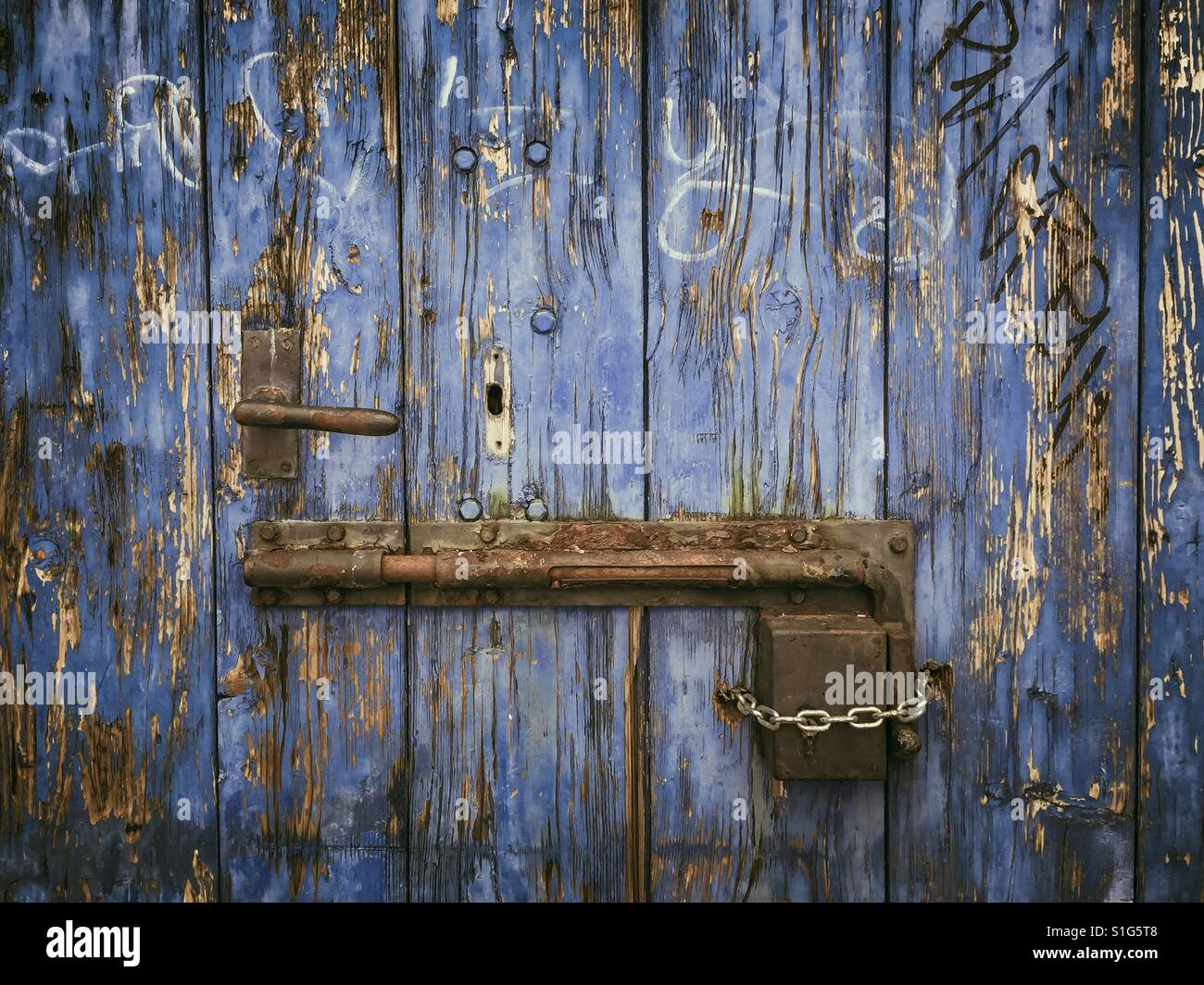 Rostige Schiebetür Schloss auf verwitterten blauen Holztür Stockbild