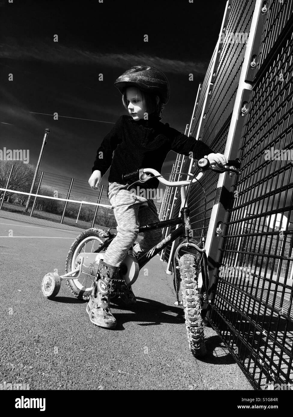 Junge Reiten Fahrrad mit Stabilisatoren Stockbild