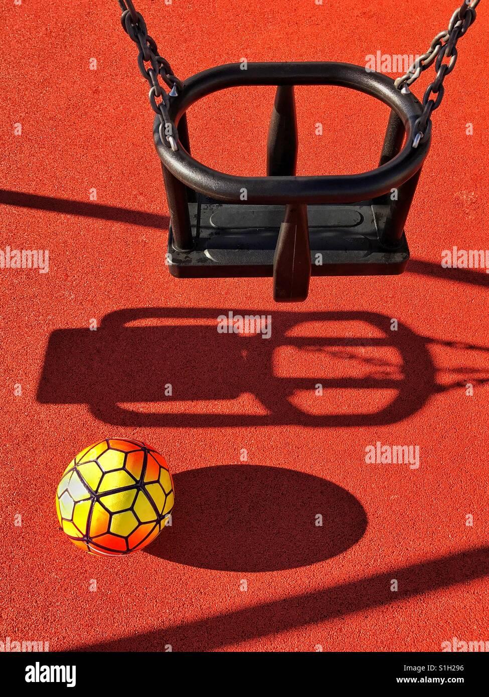 Ein einsamer Fußball sitzt unterhalb eine Einfachschaukel in einen Kinderspielplatz. Es ist eine helle Sommer Stockbild