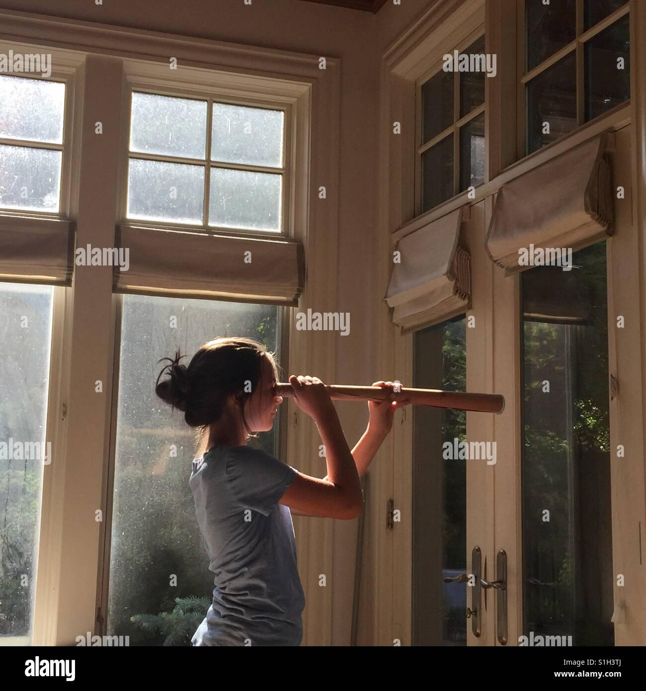 Ein junges Mädchen wird ein Papier-Teleskop für Rollenspiel verwendet. Stockbild