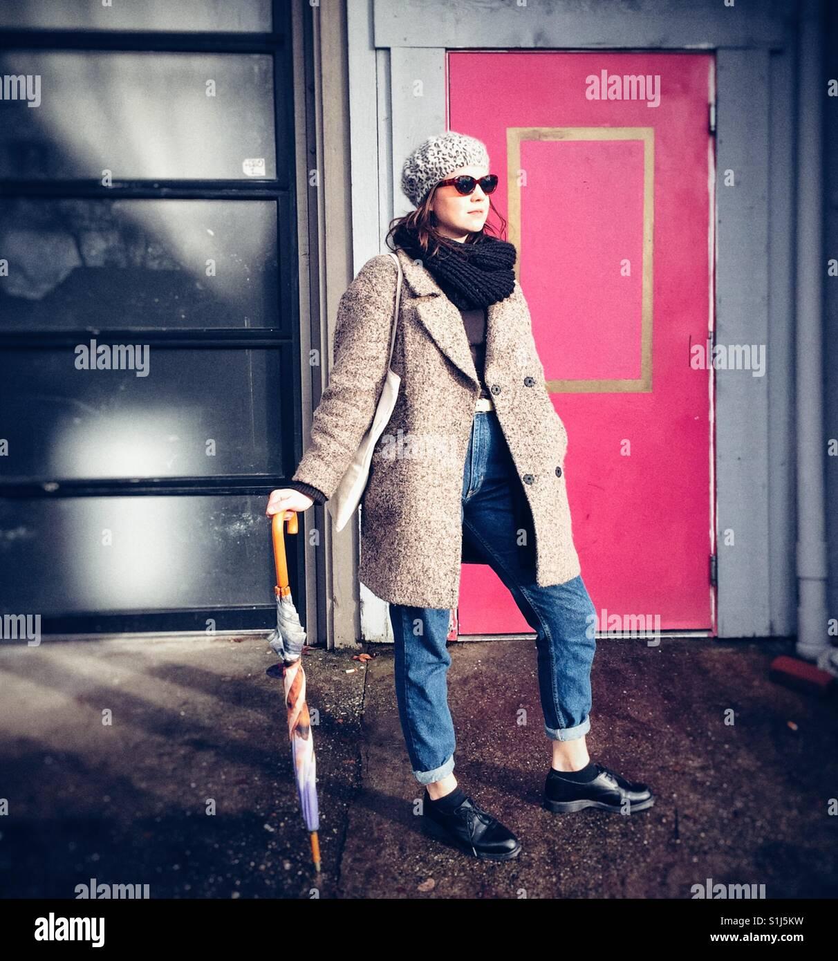 Junge modebewusste Frau trägt Barett und wolle Mantel vor rosa Tür in Seattle Stockbild