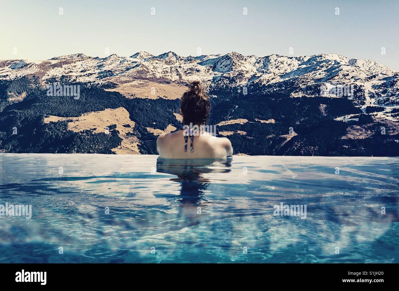 Frau Baden in einen Infinity-Pool mit Blick auf Schnee