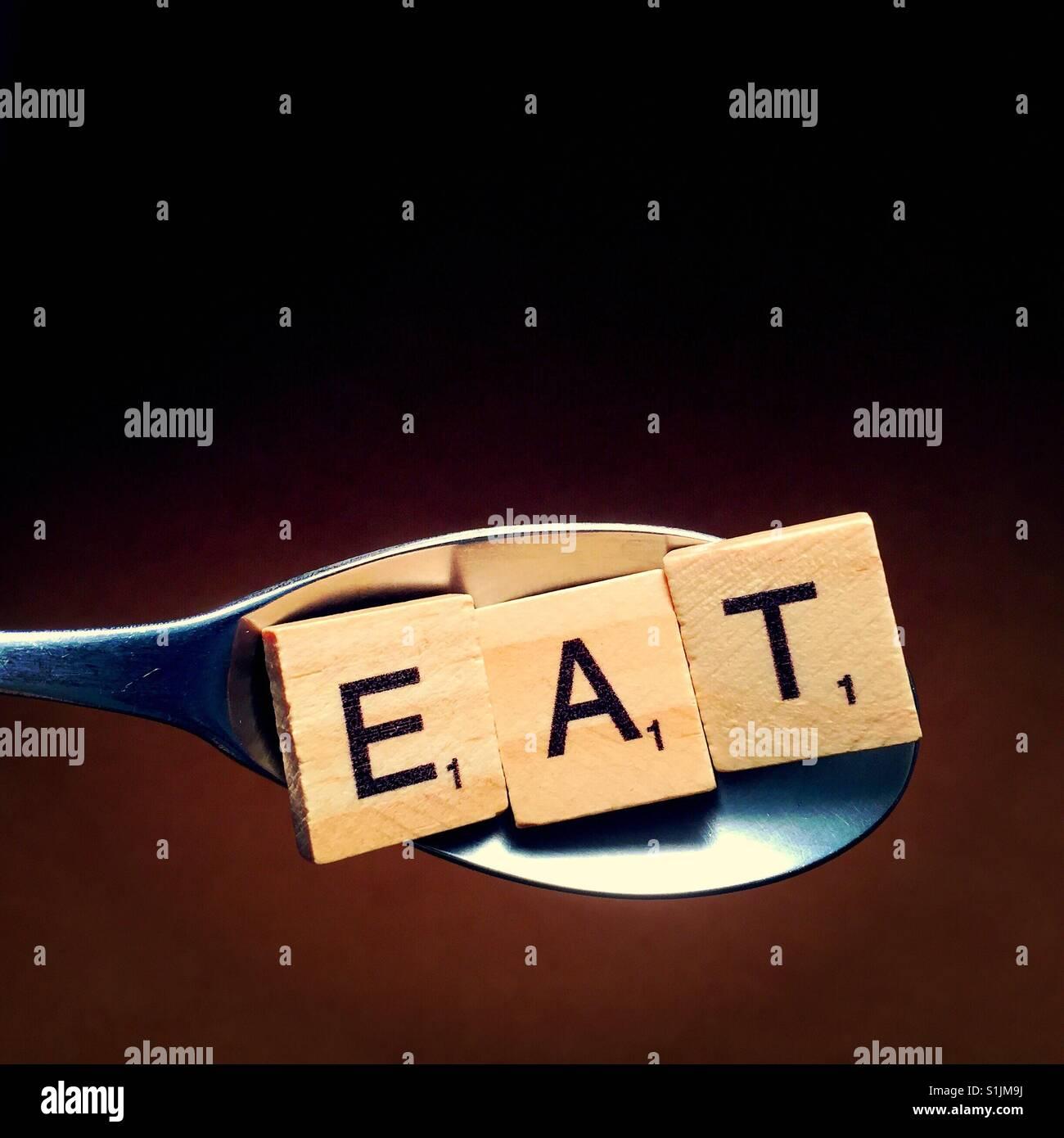 Nahaufnahme eines Löffels mit Holzbuchstaben drauf, die Schreibweise des Wortes Essen Stockbild