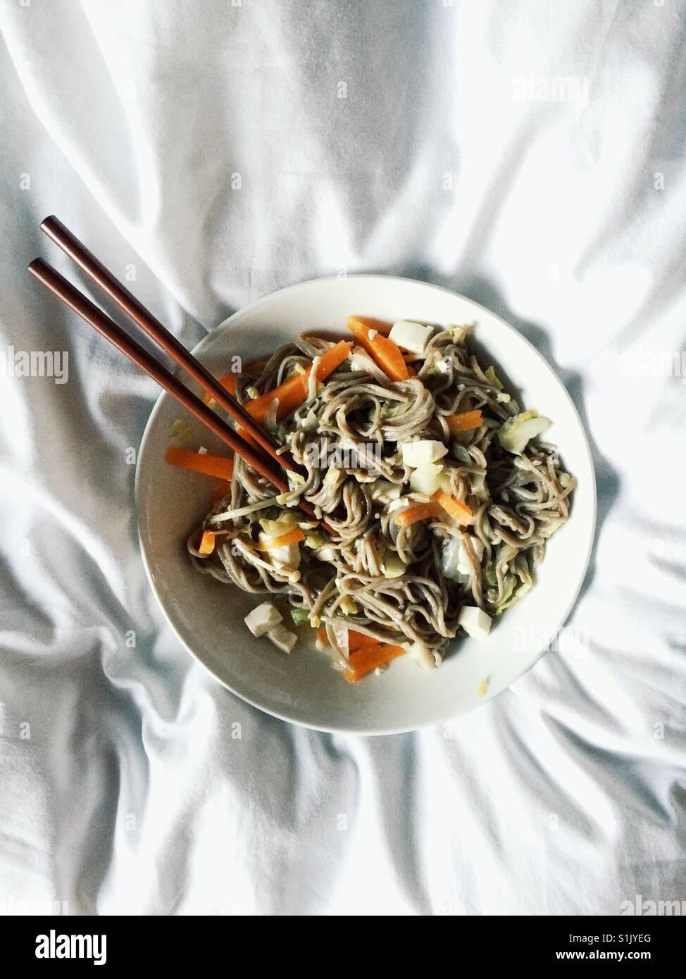 Runde weiße Schüssel mit Soba zerknittert, Nudeln und Gemüse mit Stäbchen auf weißer Bettwäsche Stockbild