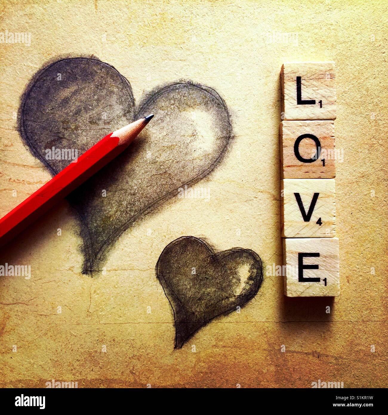Eine einfache Bleistiftzeichnung zweier Herzen mit einem Bleistift und das Wort Liebe buchstabiert mit Holzbuchstaben Stockbild
