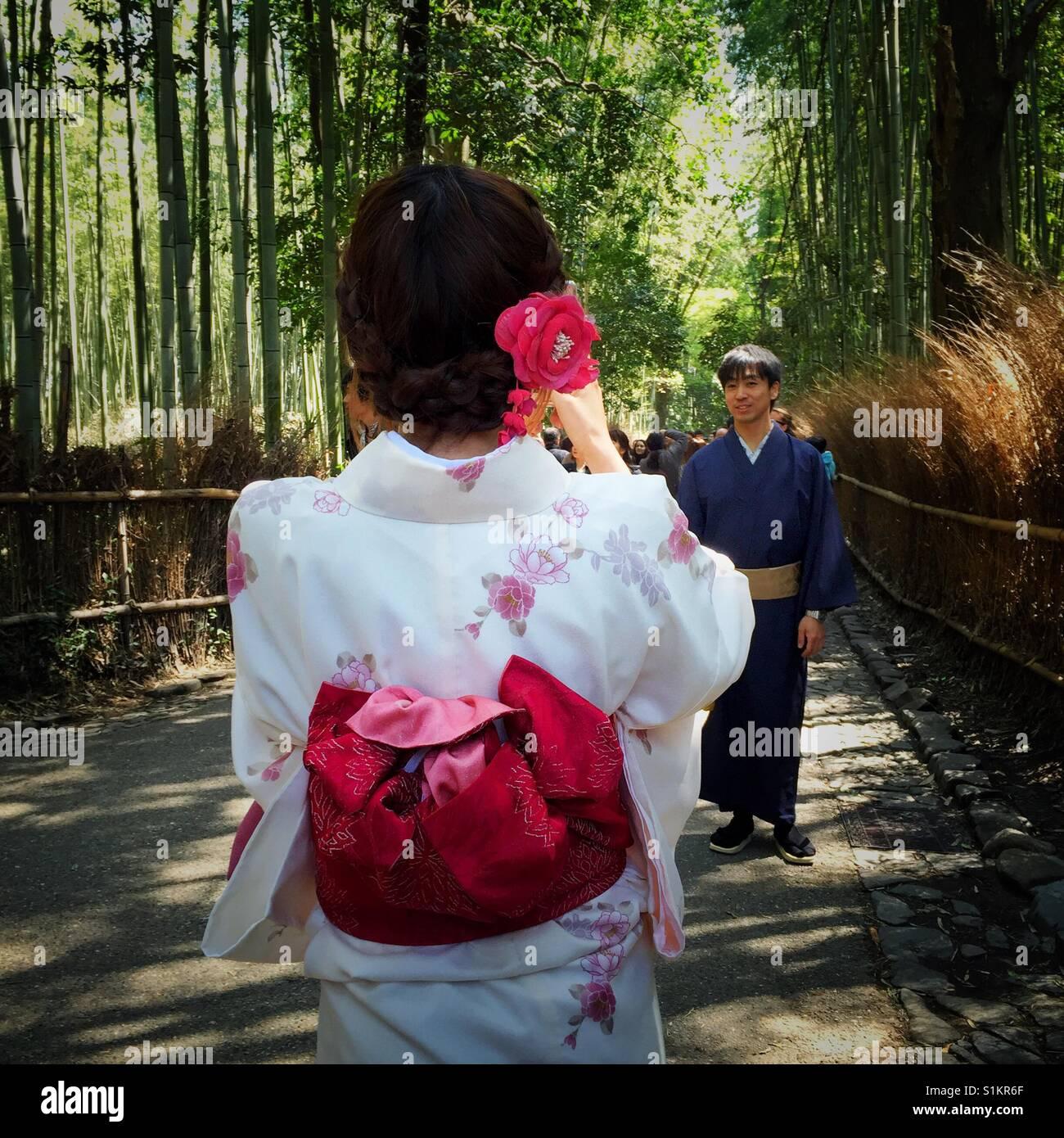 Gekleidet in traditionellen Kimono junge Japanerin unter Bild von ihrem Freund im Bambusgarten in Kyoto Stockbild