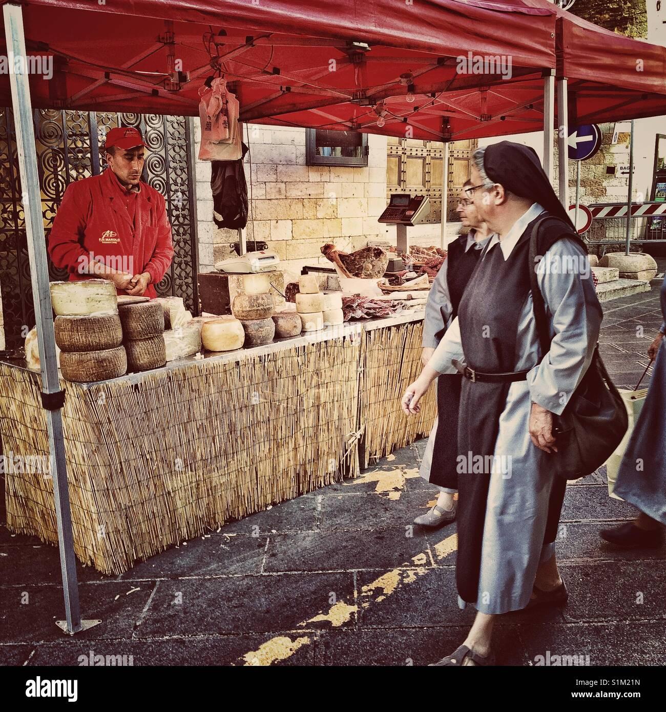 Franziskanerinnen eyeing der Käse auf dem Markt in Assisi, Italien. Stockbild