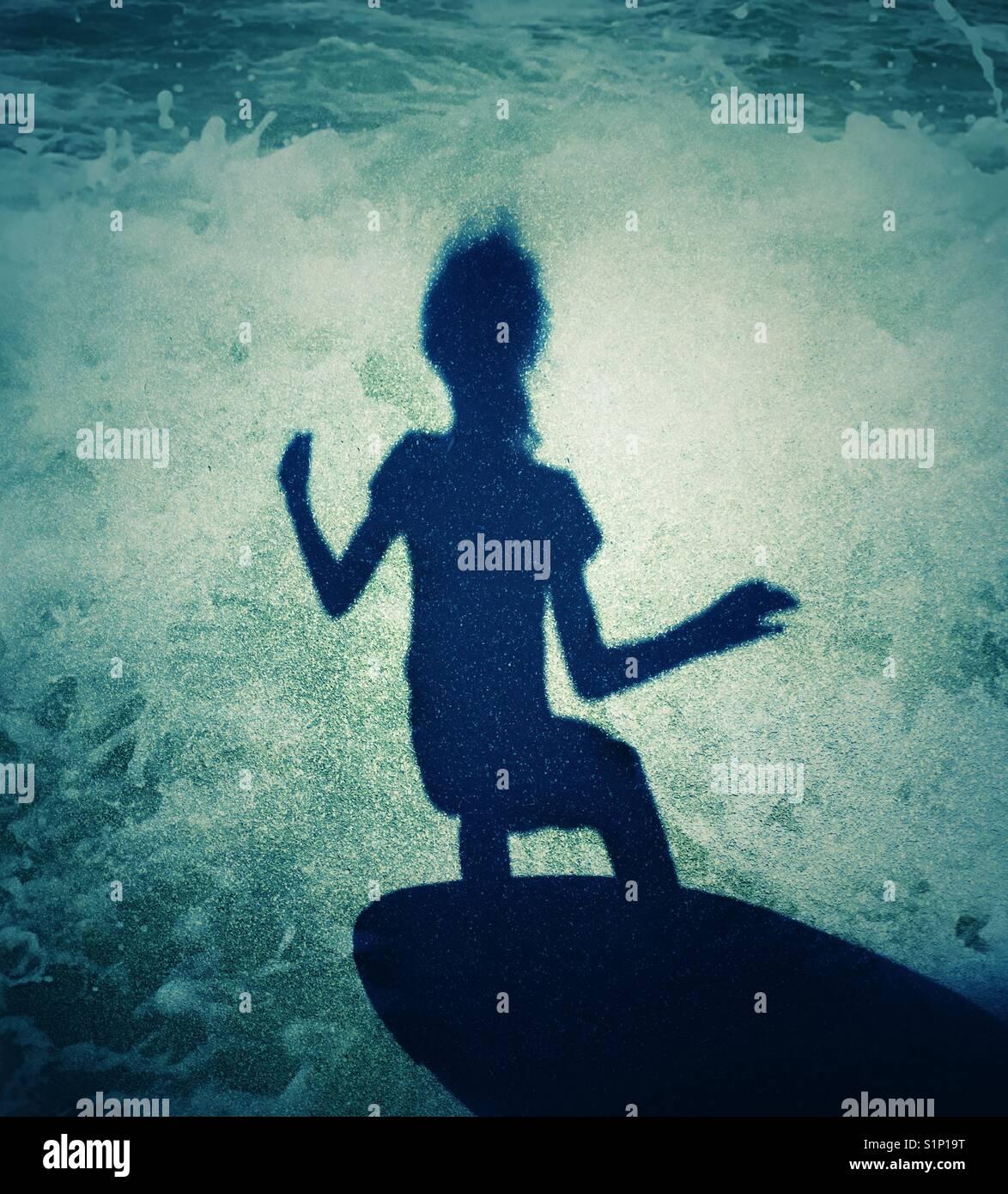 Schatten von jungen Mädchen surfen vor dem Hintergrund der brechenden Wellen Stockbild