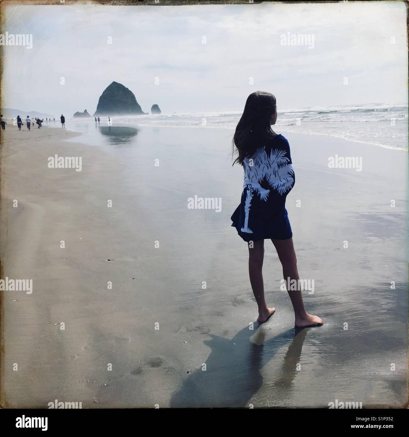 Ein Kind, das in ein Badetuch eingewickelt steht in der Nähe der Wasser in Cannon Beach, Oregon an einem Sommertag. Stockbild