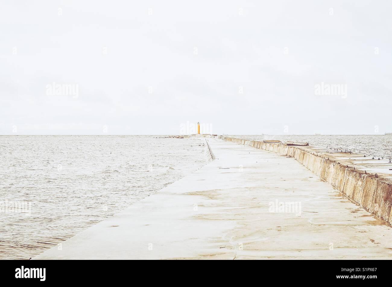 Ein Leuchtturm weit entfernt im Meer. Stockbild