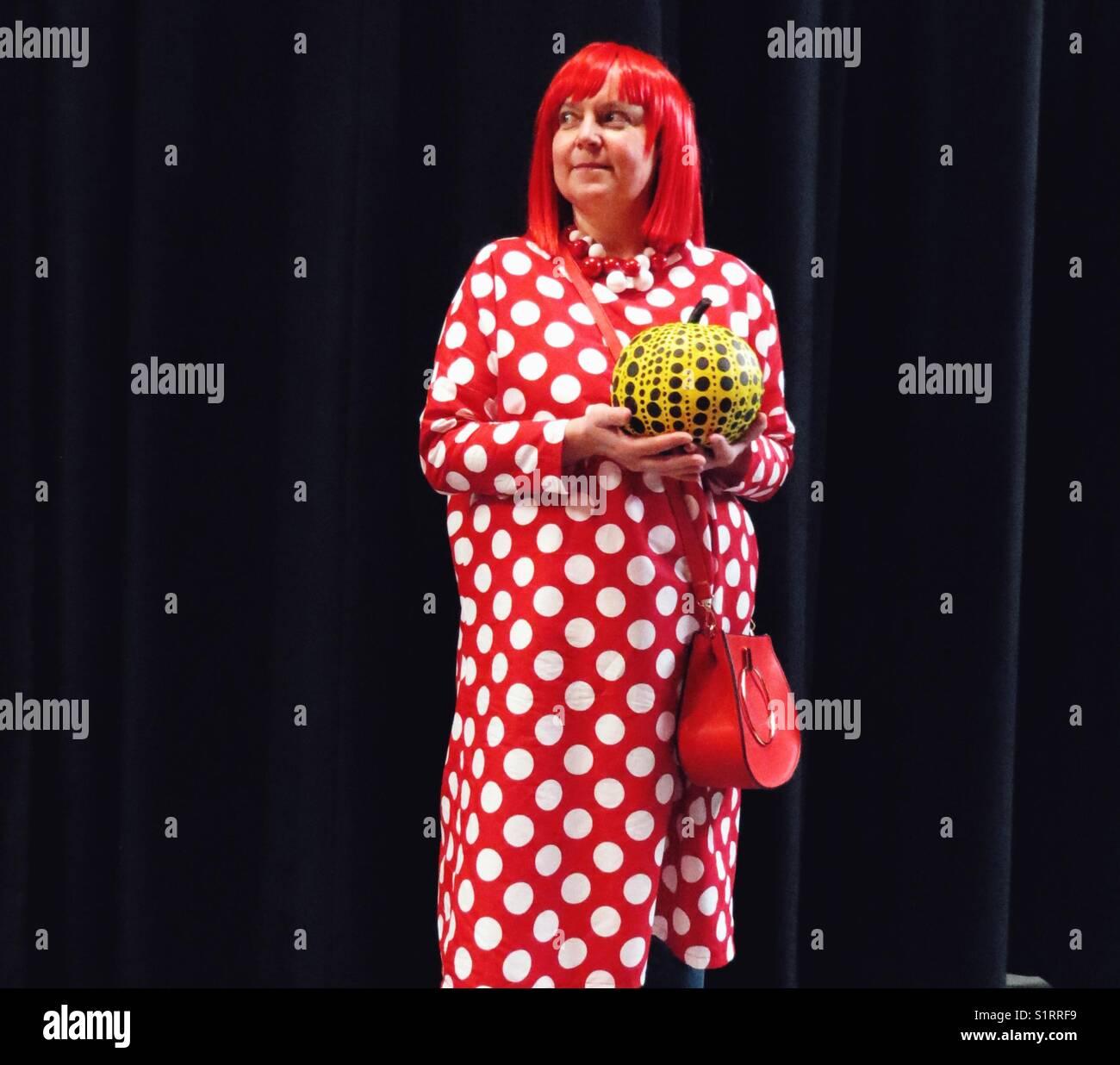 Kaukasische Frau mittleren Alters der japanischen Künstlerin Yayoi Kusama Holding gepunktete Kürbis für Stockbild