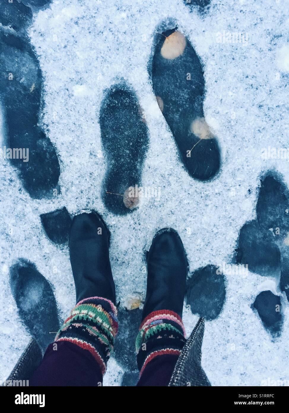 Stiefel und Gestrickte Beinlinge stehen auf dem Bürgersteig mit dem ersten Schnee und Spuren Stockbild