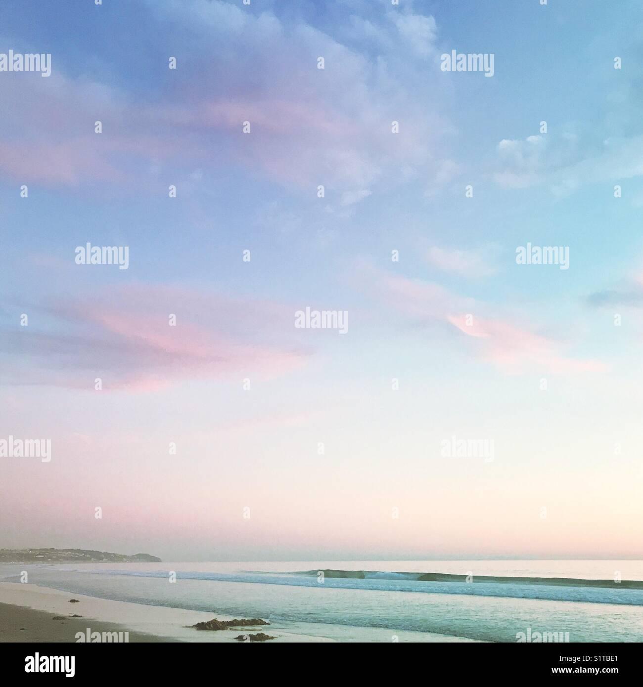 Rosa und Blau pastell Himmel und Meer Strand Landschaft stummgeschaltet. Stockbild