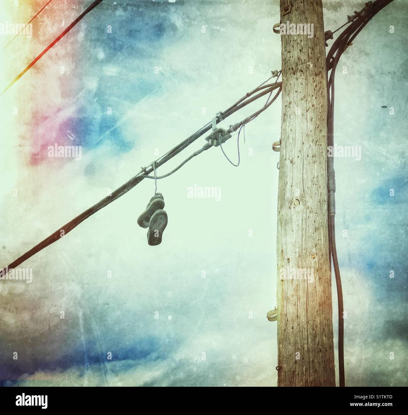 Laufschuhe hängend an einer elektrischen Leitung neben einem hydro ...