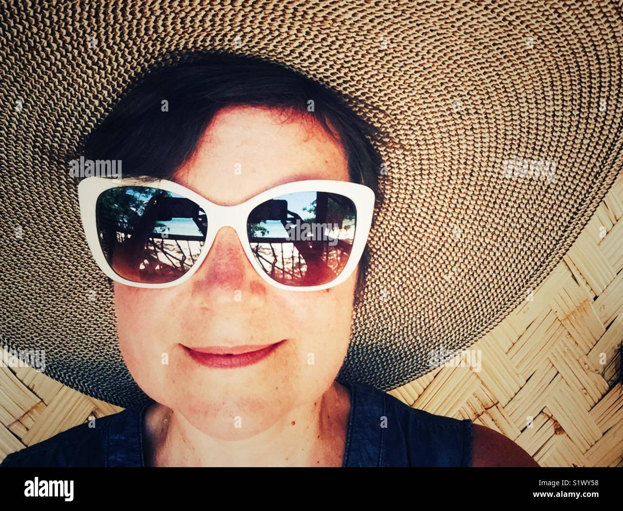 Glücklich lächelnde Frau in großen Sonnenhut und 50-s Stil weiß umrandet Sonnenbrille Stockbild