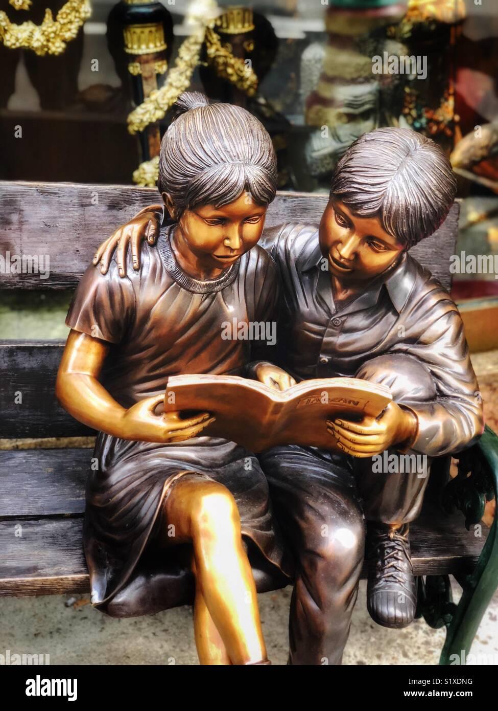 Kind Statue anschickt, ein Buch, während auf einer Bank sitzen. Stockbild