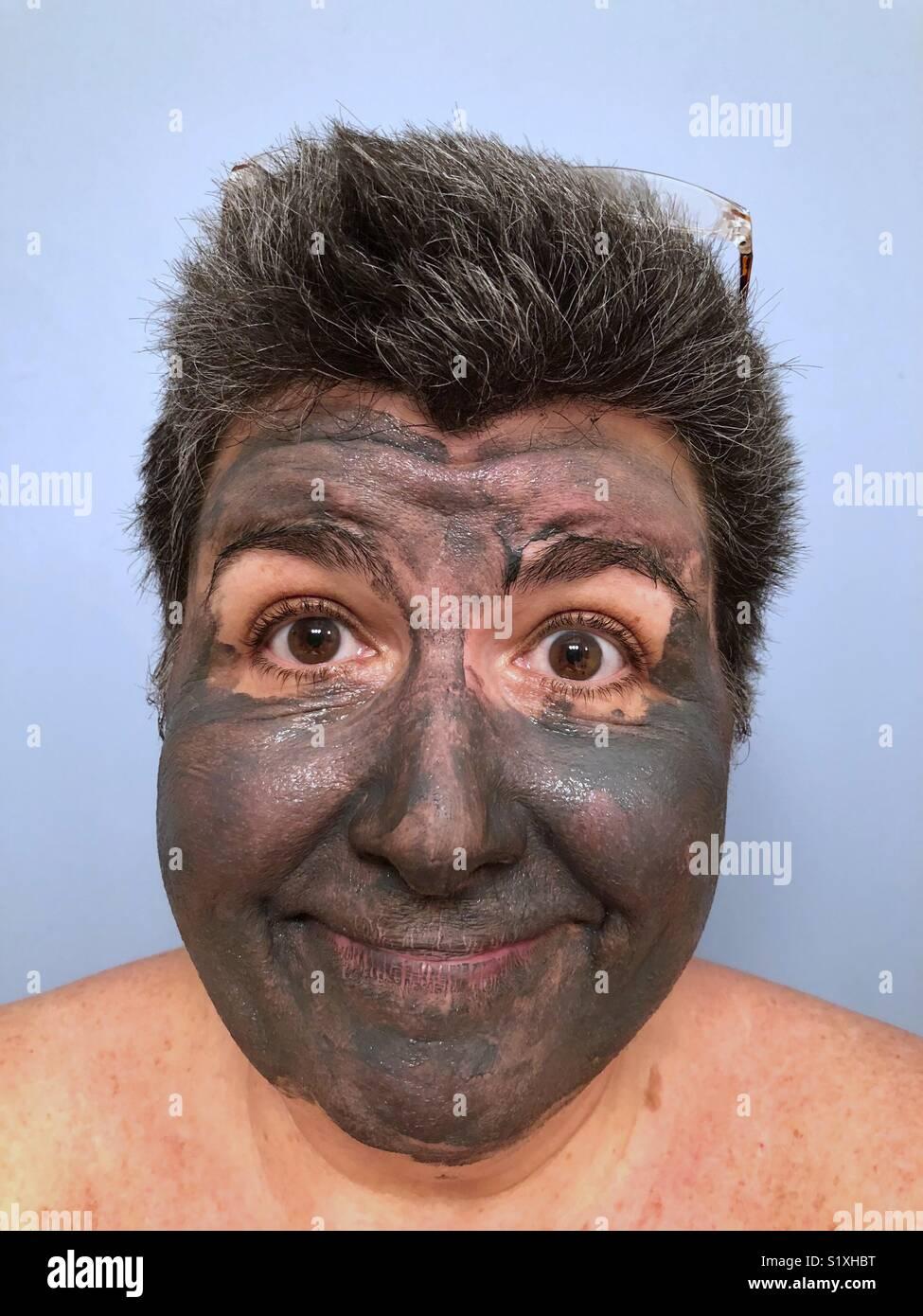 Das Porträt einer dunkelhaarigen kaukasische Frau im Schlamm Maske und lächelnd Stockfoto